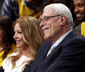 Former Los Angeles Lakers coach Phil Jackson (R) sits with Lakers Executive Vice President of Business Operations Jeanie Buss during their NBA basketball game against the Dallas Mavericks in Los Angeles April 2, 2013. Jackson was in attendance for a halftime ceremony to retire jersey #34 in honor of former Lakers player Shaquille O'Neal. REUTERS/Danny Moloshok (UNITED STATES - Tags: SPORT BASKETBALL)