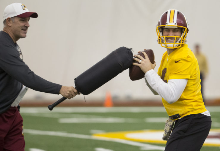 Washington Redskins quarterback Kirk Cousins, right, works with quarterbacks coach Matt Cavanaugh on a ball protection drill during practice at the team's NFL training facility at Redskins Park, on Friday, Jan. 8, 2016, in Ashburn, Va. The Washington Redskins will play the Green Bay Packers in a wild-card game on Sunday. (AP Photo/Evan Vucci)