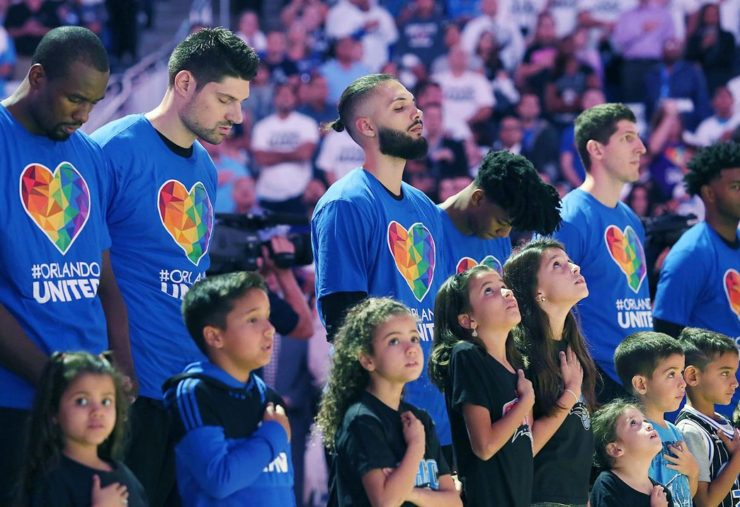 Orlando Magic players wear Orlando United shirts as they bow their heads during the national anthem Wednesday. (Stephen M. Dowell / Orlando Sentinel)